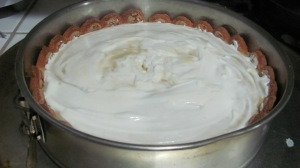 Stir sour cream and spread it on top of cheesecake starting from the outter edges and moving inward.